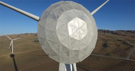 """风力发电场的风并不是所有时间都是10级以上,如何利用微风,通用电气(GE)想了个解决方法,在发电机前装了一只大鼻子,它是一个可转动的铝制盖子,可以""""收集""""微风使其直接传到叶片上,提升效率。"""
